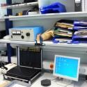 An das kleine schwarze Ding unten in der Bildmitte werden die Handys zur Analyse angesteckt. Im Koffer links daneben befinden sich diverse Anschlusskabel.
