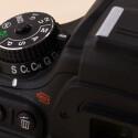 Programm- und Aufnahmewahlrad sind beide arretiert und befinden sich wie bei anderen Nikon DSLRs auf der linken Seite.