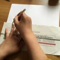 Dann nehmt ihr einen Bleistift und zieht an der Kante des Zeitungspapiers eine Linie auf das weiße Blatt.
