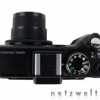 Trotz kleinen Batteriegriffs eine Kompaktkamera. Das Wählrad bietet sogar Platz für zwei vom User eingestellte Modi. Der Zubehörschuh bietet Platz für externe Blitzgeräte und anderes Zubehör.