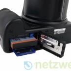 SD- oder SDHC-Speicherkarte und Lithium-Ionen-Akku. Zum Lieferumfang gehört nur ein Netzadapter um die Batterie direkt in der Kamera aufzuladen.