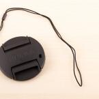 Dem Objektivdeckel liegt eine dünne Schlaufe bei, die am Kameragurt befestigt werden kann. So geht auch in Eile der Deckel nicht so schnell verloren. (Bild: netzwelt)