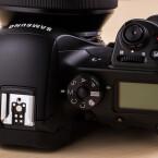 Auf der Oberseite ist ein LC-Display verbaut. Über den Blitzschuh können Aufsteckblitze angeschlossen werden. Der Kameragriff ist Samsung sehr gut gelungen.