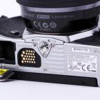 Das Stativgewinde sitzt in der optischen Achse. auf der Unterseite sind die Kontakte für den Batteriegriff und das Akkufach.