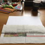 Anschließend kommt das weiße Blatt Papier ins Spiel. Schiebt dieses unter den eben hochgeklappten Teil, bis es nicht mehr weiter geht.