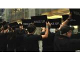 """Bild: Schwarz gekleidete Menschen halten vor dem Apple-Store schwarze Schilder hoch, auf denen schlicht """"Wake up"""" steht."""