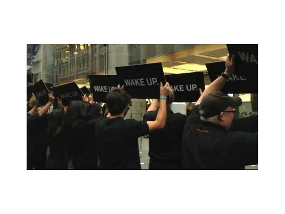"""Schwarz gekleidete Menschen halten vor dem Apple Store schwarze Schilder hoch, auf denen schlicht """"Wake up"""" steht."""