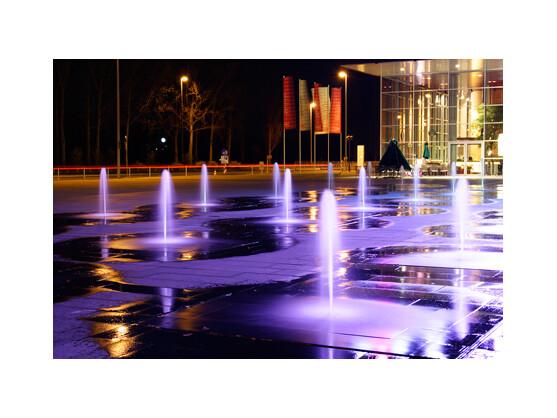 Am Abend geht an unzähligen Stellen in der Stadt das Licht an. Viele Gebäude sind, sobald es dunkel wird, effektvoll beleuchtet. Diese Wasserspiele gibt es im Sommer vor den Gebäuden von T-Com in Bonn zu bewundern. Ein Stativ und eine lange Verschlusszeit liefern dieses Ergebnis - Belichtungszeit drei Sekunden.